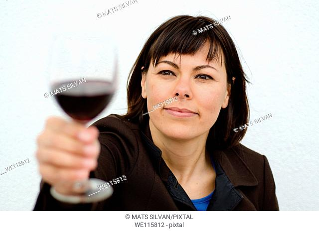 Woman holding up a glass of red wine