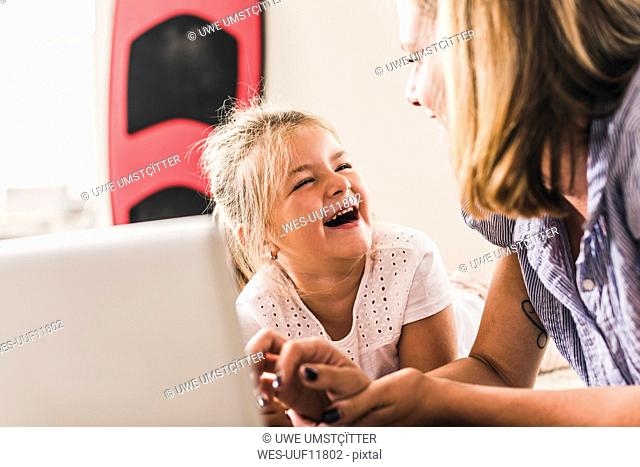 Mother and daughter having fun, using laptop