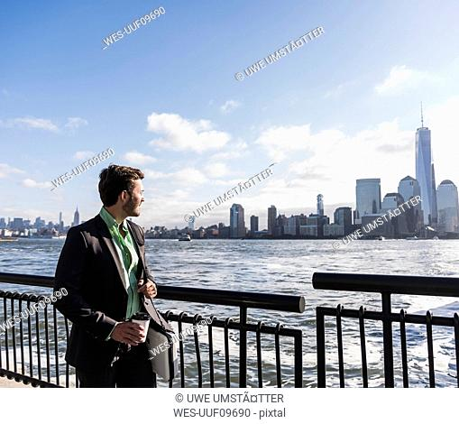 USA, businessman at New Jersey waterfront with view to Manhattan