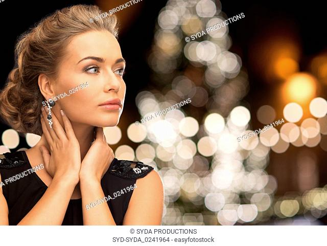 woman wearing jewelry over christmas lights