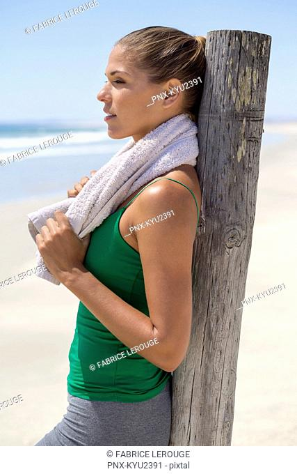 Woman leaning against a wooden post on the beach
