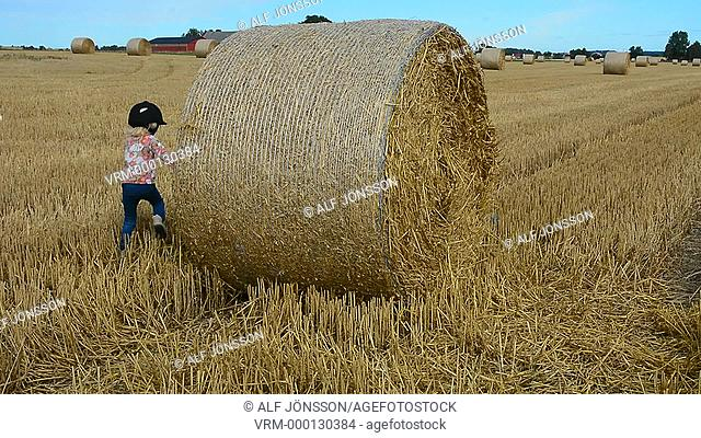 Girls play at bales of straw