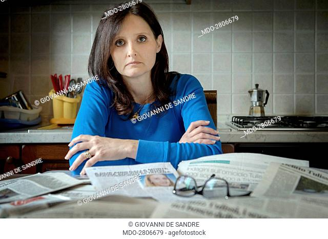 A woman sitting behind a kitchen table covered by newspaper cut out. San Giovanni al Natisone (Udine), 15th October 2014
