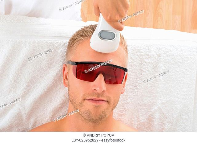 Beautician Giving Laser Epilation Treatment On Young Man