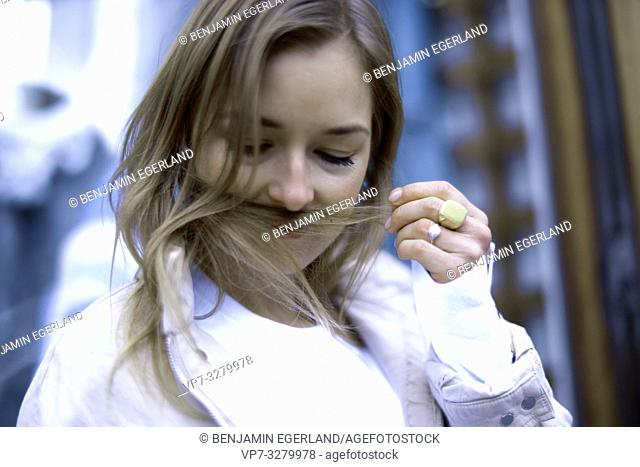 stylish woman smelling her hairs, in Paris, France