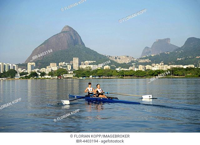 Two young women participating in early morning rowing training in the Lagoa Rodrigo de Freitas Lagoon, with Rio de Janeiro skyline and Sugar Loaf Mountain