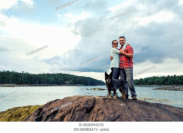 Portrait of romantic mid adult couple and dog on rock at coast of Maine, USA
