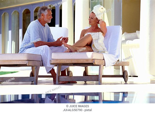 Mature man and woman sitting outside at spa