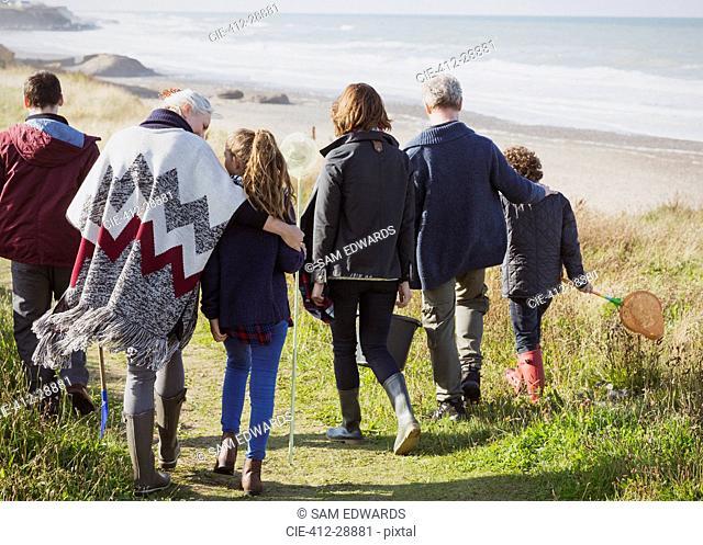 Multi-generation family walking on sunny grass beach path