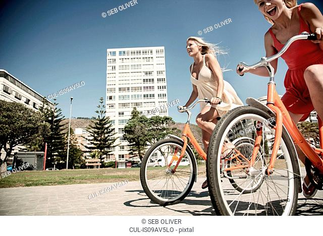 Young women cycling past buildings, Cape Town, South Africa