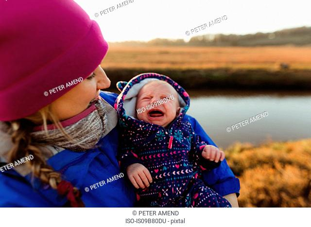 Mid adult woman cradling crying baby daughter on riverbank, Morro Bay, California, USA