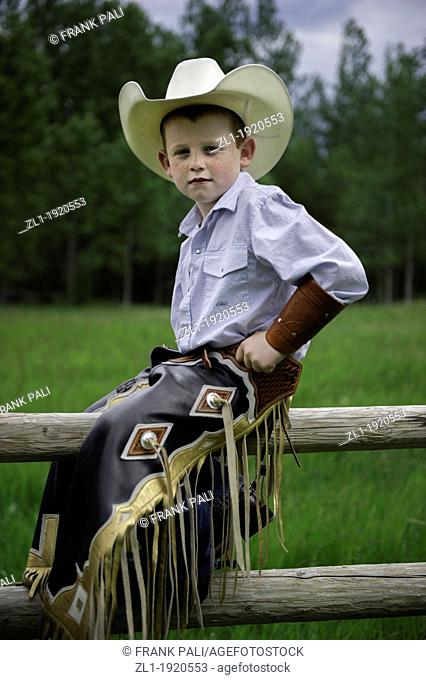 Young cowboy on fence with his western clothing.Telkwa, British Columbia