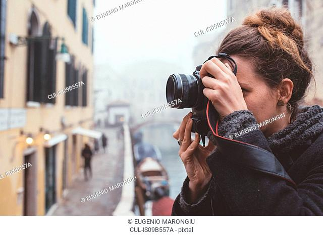 Young woman photographing on misty canal waterfront, Venice, Italy