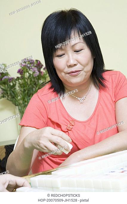 Mature woman playing mahjong