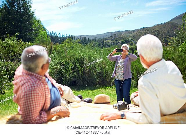 Active senior woman with camera phone photographing men relaxing on sunny summer picnic blanket