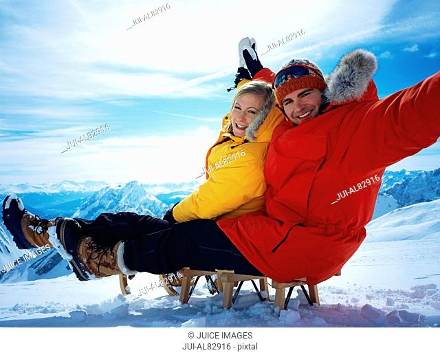 Couple sitting on sled on snowy mountain