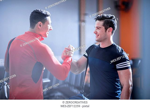 Two young men shaking hands in gym