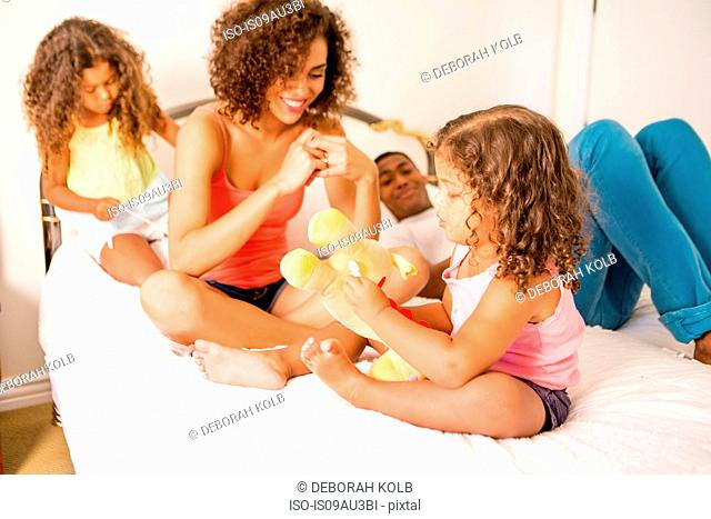 Family sitting on bed talking, smiling