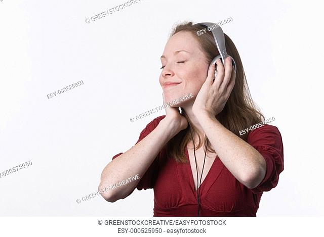 a young woman joyfully listens to music on headphone while her hands hold the earpieces