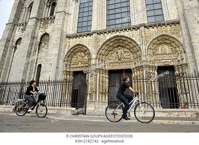 young women cycling in front of the West facade of the Cathedral of Our Lady of Chartres, Chartres, Eure & Loir department, region Centre, France, Europe