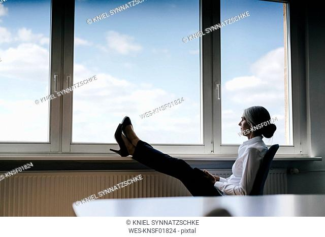 Businesswoman in office sitting at the window looking out