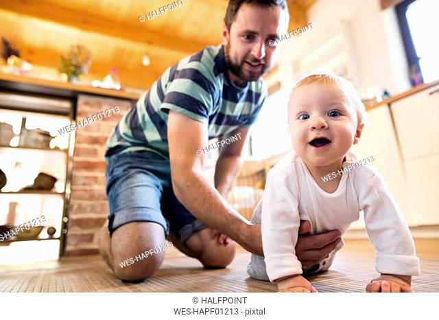 Father supporting crawling baby at home