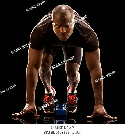 African American runner crouching at starting block