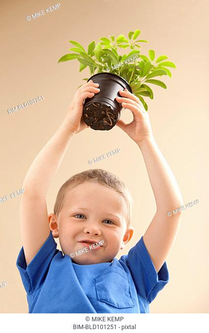 Caucasian boy holding potted plant