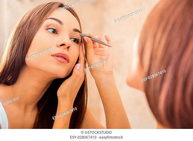Tweezing eyebrows. Beautiful young woman tweezing her eyebrows while looking at the mirror