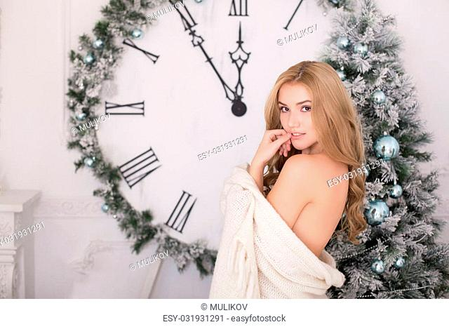 Beautiful young blonde woman wrapped in a blanket over Christmas tree