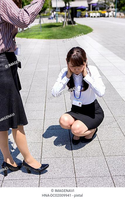 A business woman being angry and the another woman covering her ears