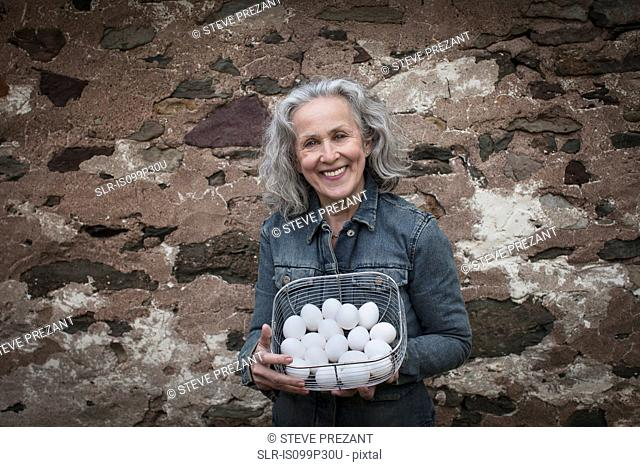 Senior woman with basket of eggs