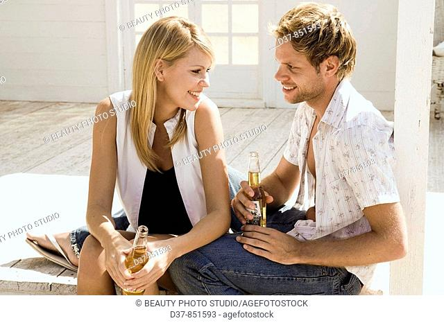 Young couple talking and drinking a beer