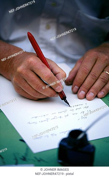 The hands of a woman writing a letter