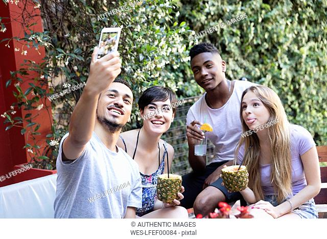 Happy friends having cocktails and taking a selfie outside