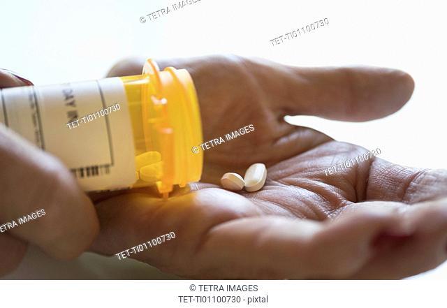 Female hand holding pill bottle
