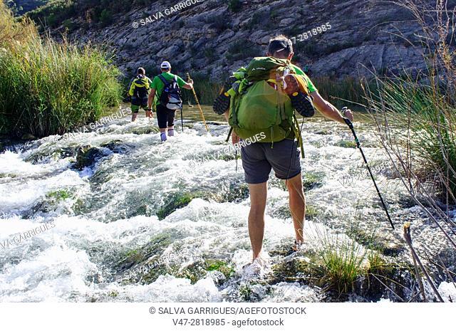 Walkers crossing the river Jucar in Millares, Valencia, Spain