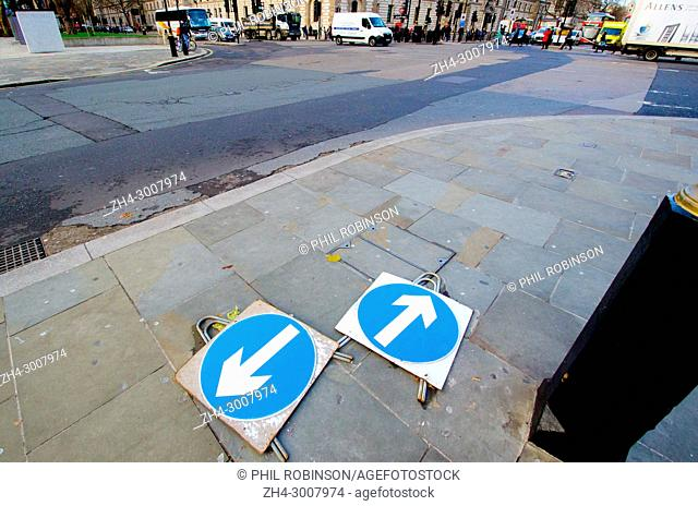 London, England, UK. Traffic arrow signs lying flat on the pavement pointing in different directions, in Parliament Square