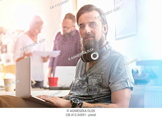 Portrait smiling male design professional with headphones using laptop in office