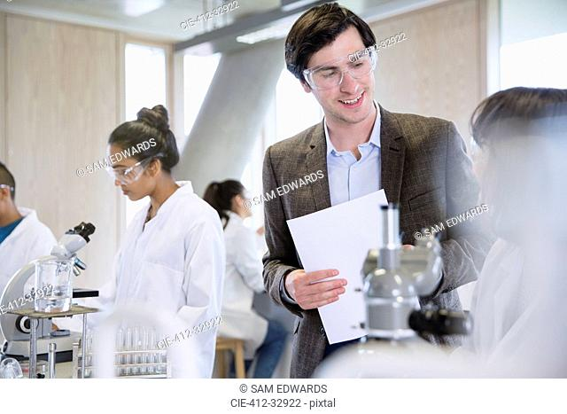 Science professor helping college student in science laboratory classroom