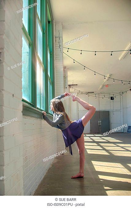 Teenage girl looking through dance studio window poised, holding raised leg