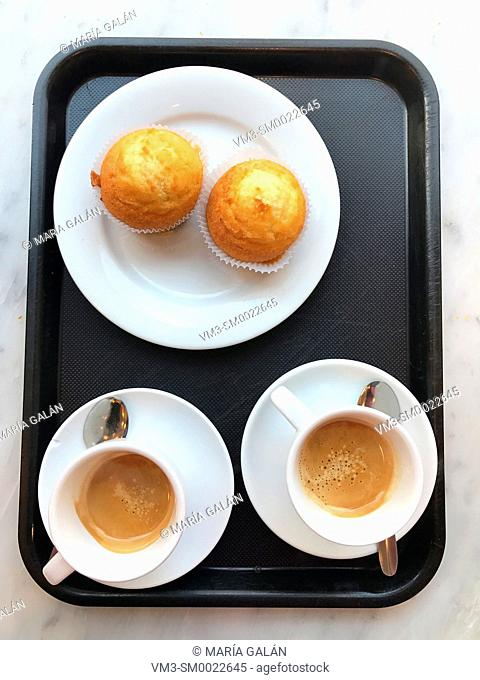 Two cups of coffee and two sponge cakes on tray. View from above