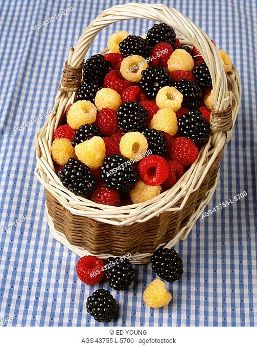 Agriculture - Red raspberries, golden raspberries and blackberries in a basket on a blue checkered tablecloth
