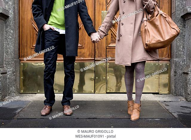 Businessman and businesswoman hand in hand in front of a gate