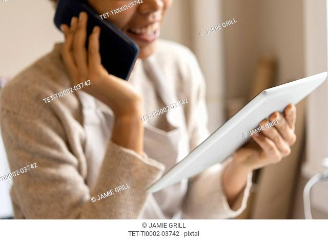 Young woman using digital tablet while taking phone call