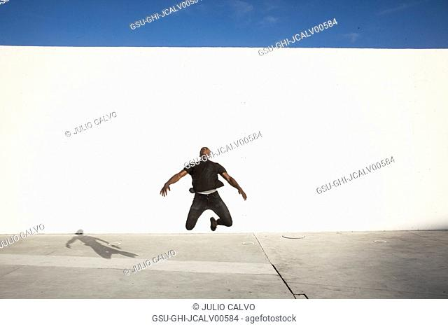 Young Adult Man Jumping in Air with Large White Wall in Background