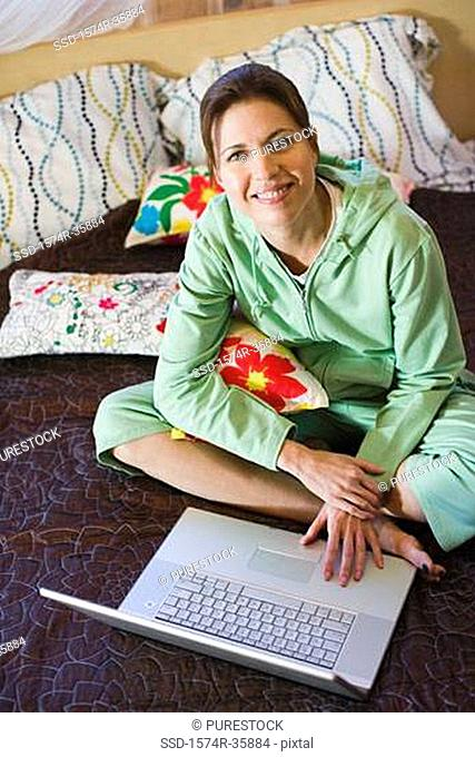 Woman working on laptop in bedroom