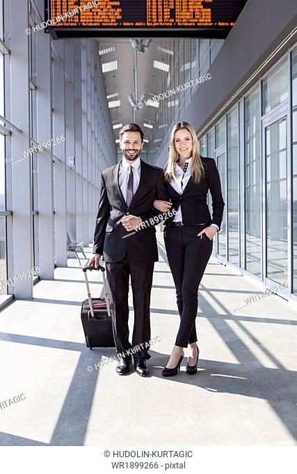 Business partners arm in arm in airport