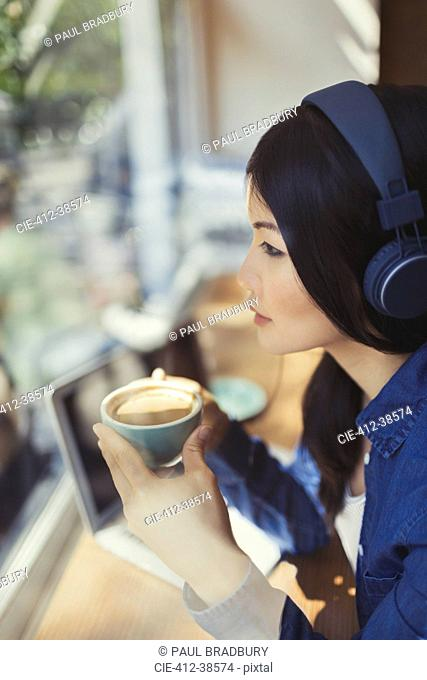 Pensive young woman drinking coffee, listening to music with headphones at cafe window