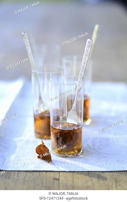 Medlars served in cognac in glasses with forks